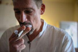 Dominique Loumachi fume une cigarette qui ressemble à du cannabis mais n'en est pas (pour ne pas tomber sous l'accusation de promouvoir l'usage de stupéfiants), le 28 février 2013 à Belfort (Photo Sebastien Bozon. AFP)